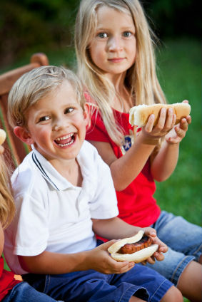 Two-kids-eating-a-hot-dog