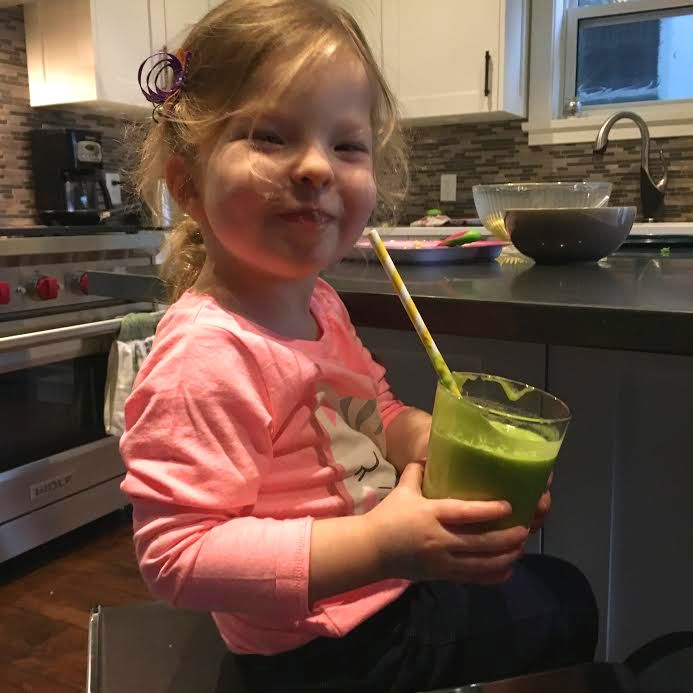 Miss Q is all smiles about her green smoothie